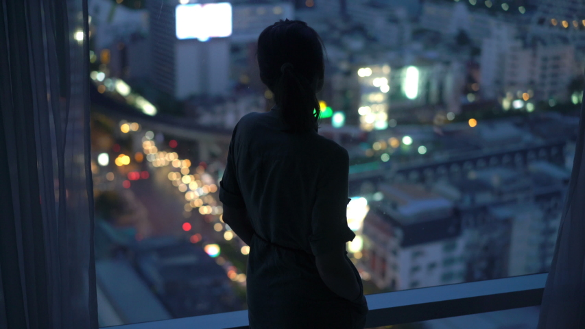 Silhouette of woman looking at city at night, standing by window at home | Shutterstock HD Video #1030263554