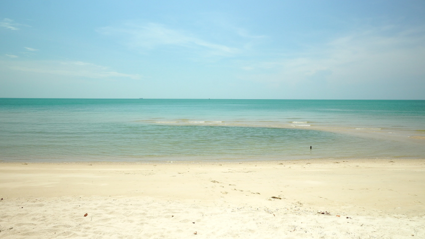 Scenic of the clean and clear ocean crashing to the tropical white sand beach on a sunny day during summer. Khanom beach Thailand with beautiful sky and clear water. | Shutterstock HD Video #1030264028