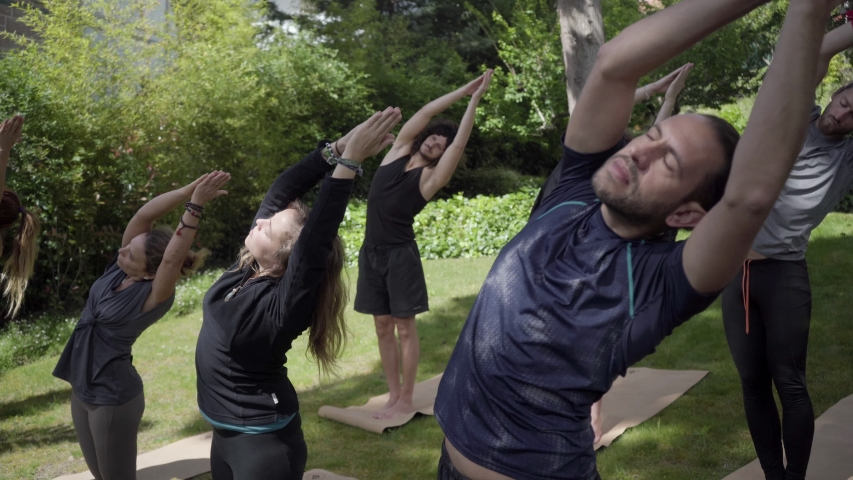Men and women practicing yoga in park. Flexible barefoot people in sportswear standing on yoga mats and training outdoor. Yoga concept | Shutterstock HD Video #1030264286