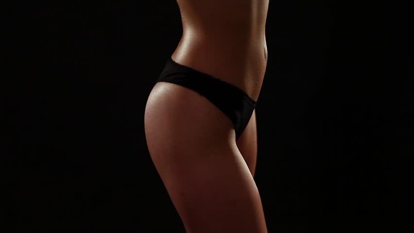 Sexy brunette woman in black lingerie dancing in studio. Black background. Low key.