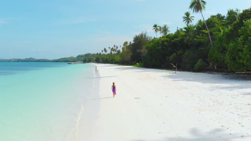 Aerial slow motion: Woman walking on white sand beach turquoise water tropical coastline Pasir Panjang Kei Islands Indonesia Moluccas Maluku Indonesia scenic travel destination