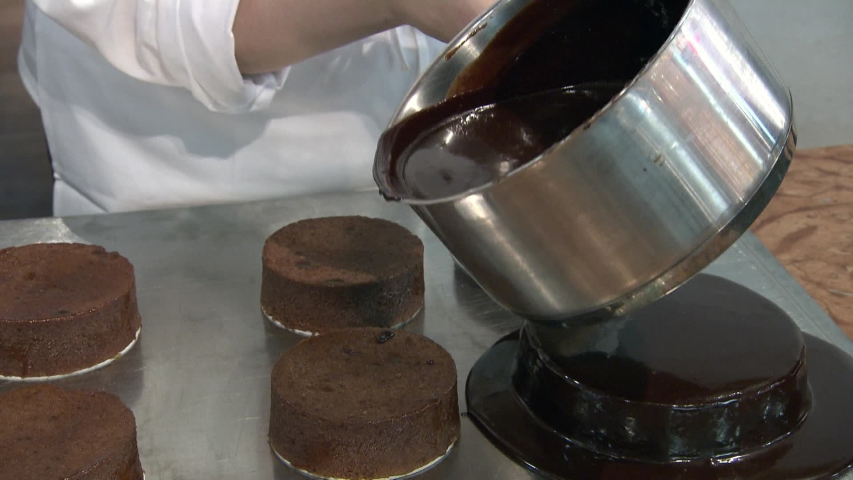 Chocolate icing on cake. Chocolate glaze pouring on homemade cake.   Shutterstock HD Video #1030276751
