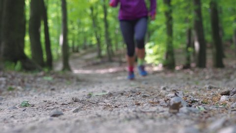 Low angle shot of a trail runner in the forest running towards the camera