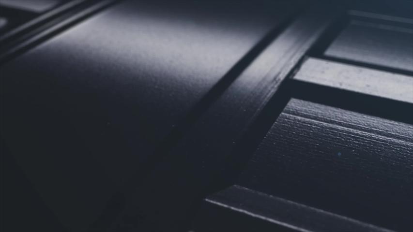 Abstract close up black metal background. Macro creative shot dark ribbon steel lines.