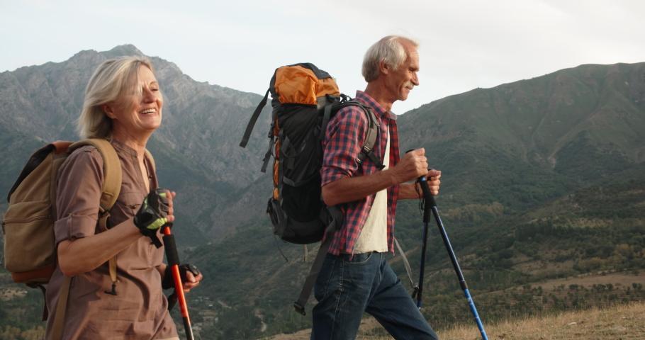 Positive mature caucasian couple trekking in mountains with backpacks, enjoying their adventure 4k | Shutterstock HD Video #1030289057