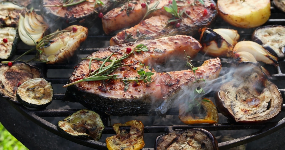 Grilled fish, grilled salmon steak with the addition of rosemary, aromatic spices and vegetables on the grill plate outdoors, close-up, 4k. Grilled seafood #1030304714