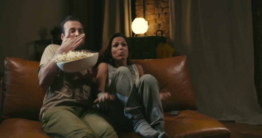 Scared caucasian couple watches movie on couch and eats popcorn at home. They spill popcorn because of unexpected scene