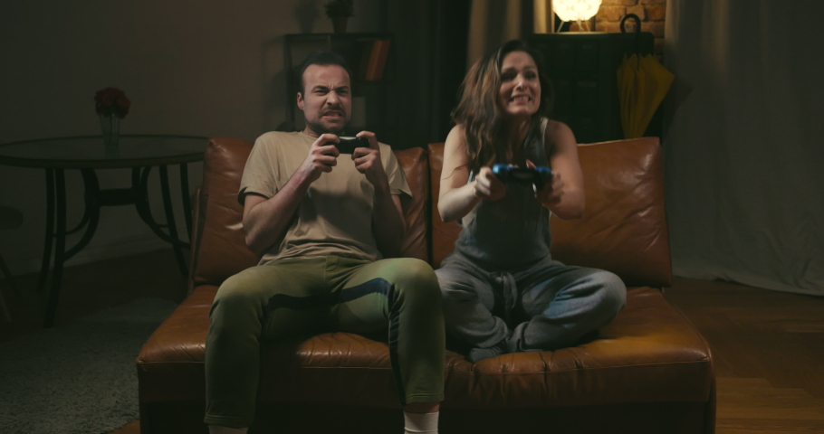 Young caucasian couple plays videogame. Young woman is happy with her victory, man on the contrary disappointed | Shutterstock HD Video #1030305770