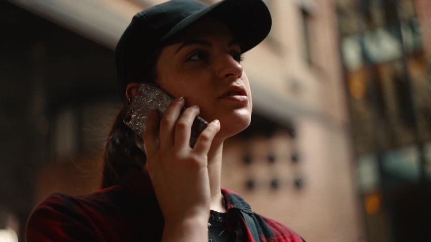 Young girl in a black cap and checkered shirt talking on the phone outdoors and using a smartphone. Building on background  | Shutterstock HD Video #1030310408