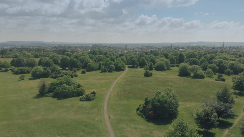 Path into the city - Pathway through green park towards a distant city on horizon | Shutterstock HD Video #1030312886