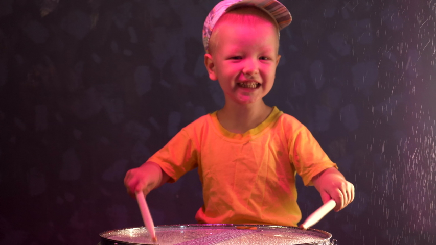 Teen blonde boy in yellow suit playing drum in rain. child holds drumsticks. Drops of water fall on drum. Splashes fly in different directions.