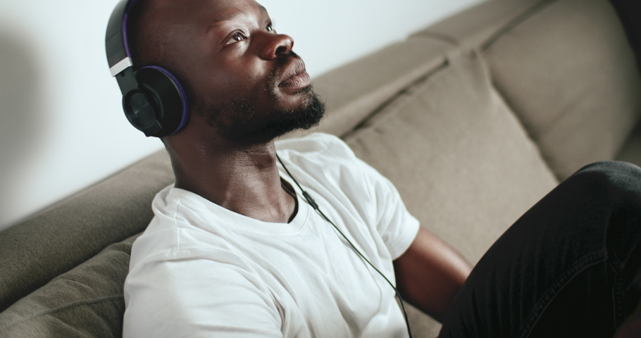 Young afro-american man dressed in white t-shirt wears headphones enjoying music sitting on grey sofa, indoors close up shot | Shutterstock HD Video #1030316867