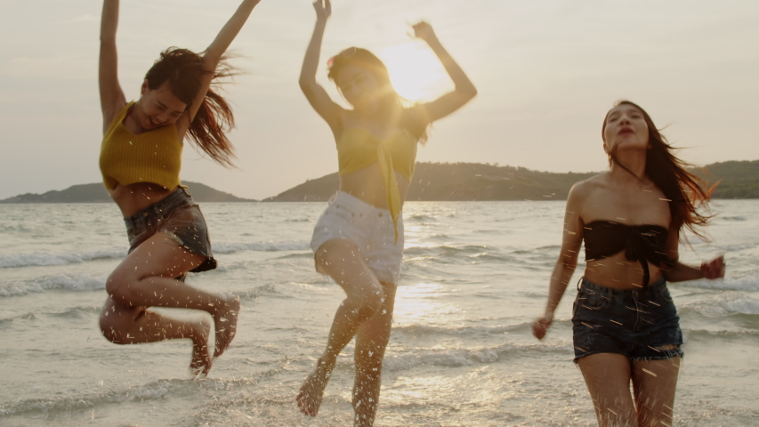 Group of Asian young women running on beach, friends happy relax having fun playing on beach near sea when sunset in evening. Lifestyle friends travel holiday vacation summer concept. 4k Slow motion.