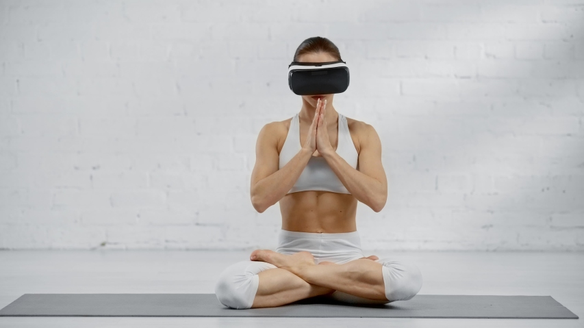Woman in vr headset sitting in lotus pose, showing namaste sign   Shutterstock HD Video #1030328531