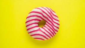 Stop motion creative concept video animation donut bite on yellow background.