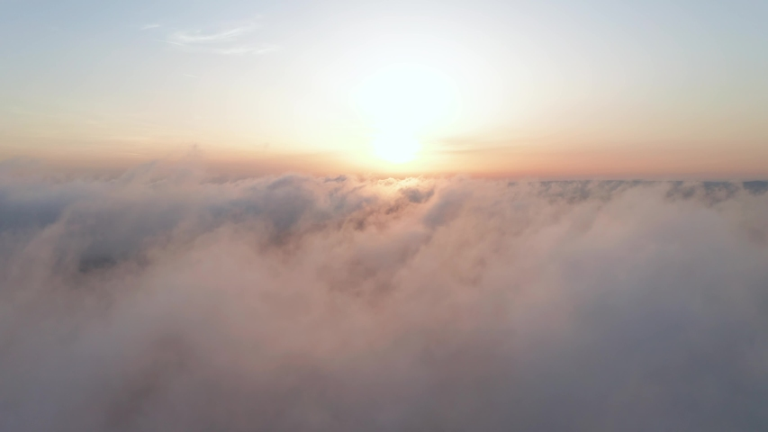 Moving white clouds blue sky scenic aerial view. Drone flies high back in blue sky through the fluffy clouds in the evening at the bright sun. Sun is hidden behind the clouds at sunset the fog