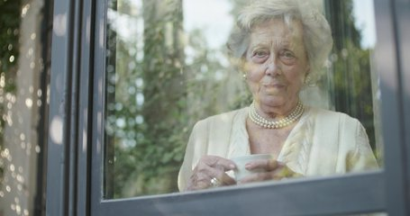 Senior grandma woman drinking cup of tea or coffee near window looking outside worried or sad or thinking.Beautiful white hair elderly grandmother portrait at home.View from outside.Slow motion video