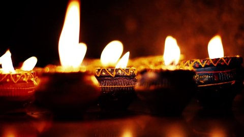 Lighted clay candle diya with selective focus and shallow depth of field in the dark