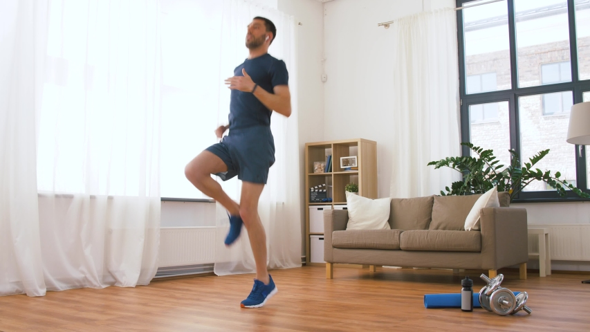 fitness, sport, technology and healthy lifestyle concept - man with wireless earphones running on spot at home #1030360058