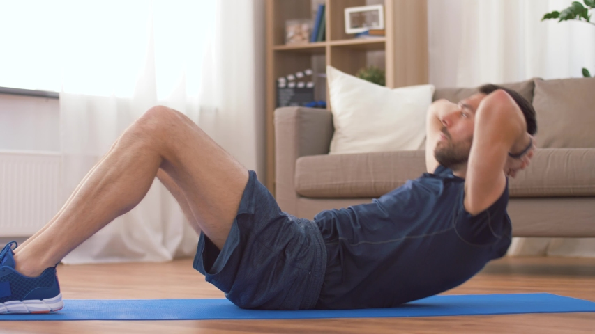 Sport, fitness and healthy lifestyle concept - man making abdominal exercises at home | Shutterstock HD Video #1030360376