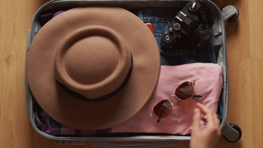 Faceless female hands packing trunk bag for travel slow motion 4k close up. Top view of unrecognizable woman putting clothes gadget devices hat sun glasses into suitcase ready for trip. Tourism summer