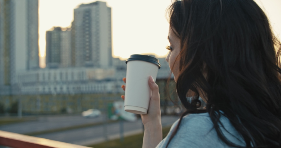 Pretty young woman drinking hot coffee from paper cup. Girl standing on city bridge in summer sunset time and enjoying view, close-up. Urban concept . 4k slow motion video footage 60 fps | Shutterstock HD Video #1030367501