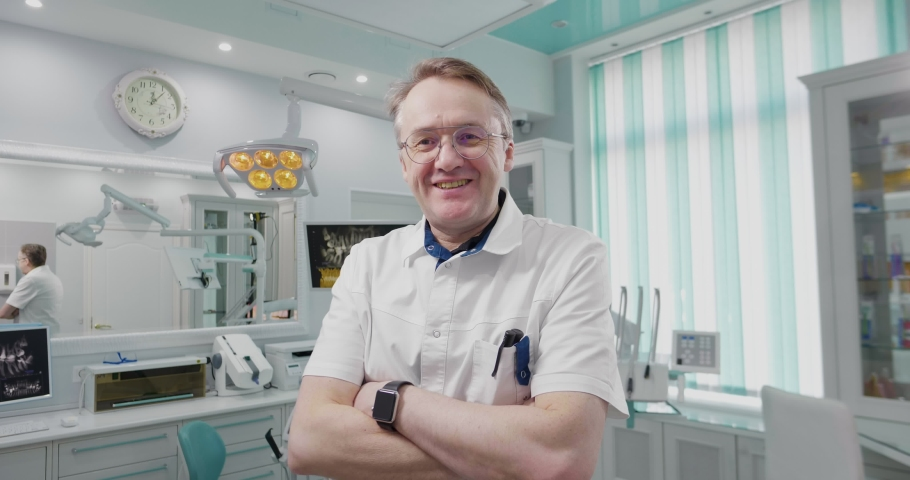 Adult male european dentist in glasses smiles. Professional caucasian doctor is confident and loves his job. Middle aged doctor in modern consulting room. Healthcare and medical insurance concept