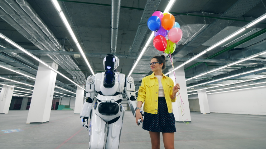 Girl with balloons and a droid walk in a room, holding hands. | Shutterstock HD Video #1030374365