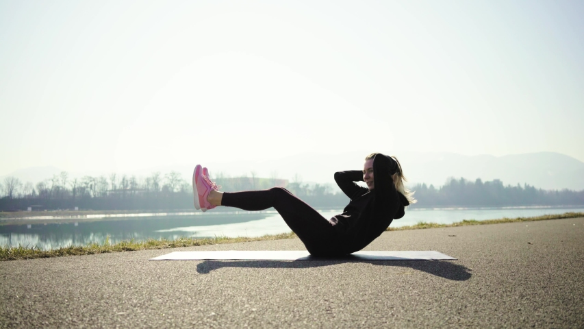 Young woman doing sports workout. 4K slow motion video. Woman running walking in outdoors park on sunny day, close-up legs sport shoes. Female exercising in the gym