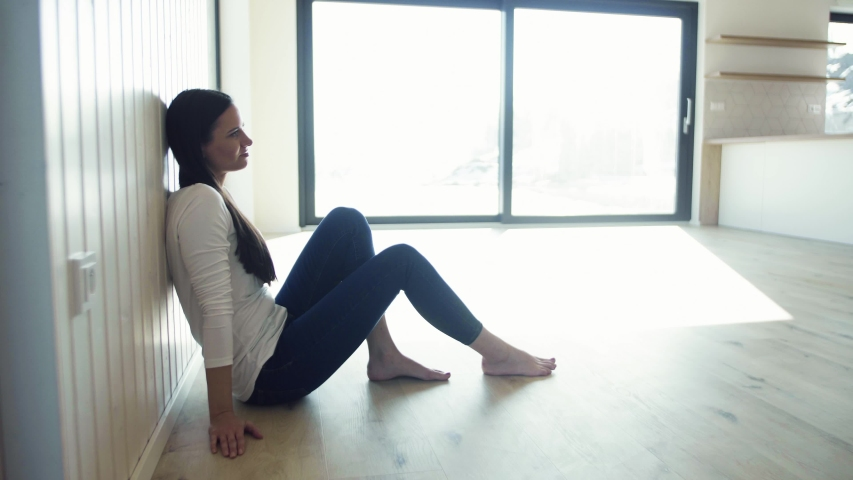 A cheerful young woman sitting on the floor in new home, resting. #1030386107