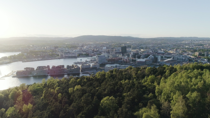 4K aerial of the Oslo city line with a backdrop of downtown Oslo and the construction of Bjoervika, a popular tourist attraction with the Munch museum, Barcode and Soerenga pier, with forward motion.
