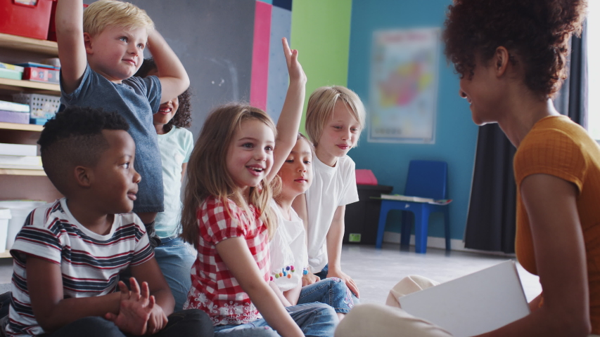 Elementary Pupils Raising Hands To Answer Question As Female Teacher Reads Story In Classroom | Shutterstock HD Video #1030387787