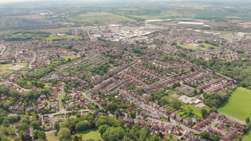 Aerial footage overlooking the British town of Castleford near Wakefield in West Yorkshire, showing rows of houses and fields in the background, taken on a sunny bright summers day. | Shutterstock HD Video #1030390211