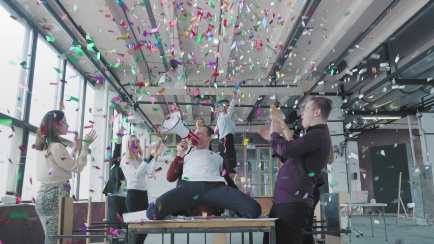 Manager start to dance on the table, sings into a megaphone, accelerates and slide on lap. Colleagues blow up flappers with confetti. Office celebration. Success. Corporate party business team | Shutterstock HD Video #1030393181