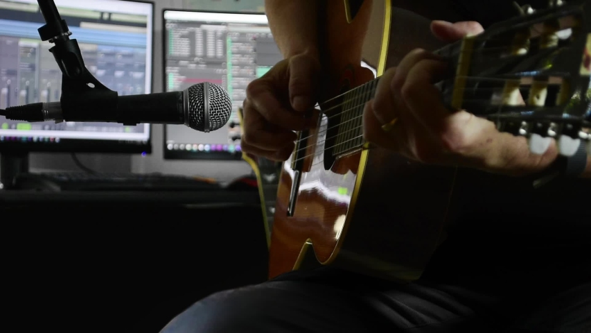 Classical guitarist records with a microphone in a home recording studio, using PC software