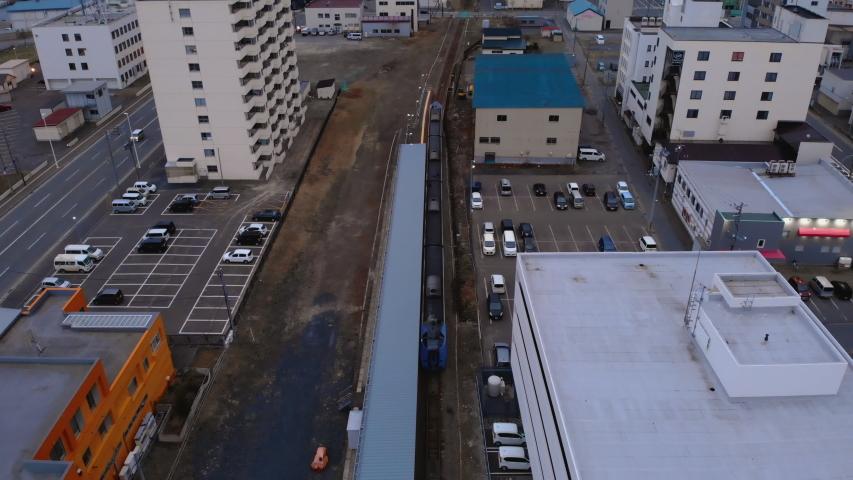 Train leaving station in Wakkanai city, S?ya - Hokkaid?, Japan - Aerial shot #1030411343