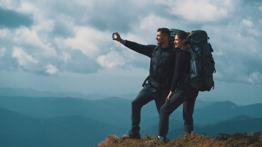 The man and woman with backpacks making selfie on the mountain | Shutterstock HD Video #1030416050