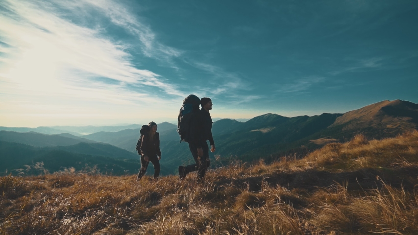 The couple walking on the mountain on a sunny background. slow motion