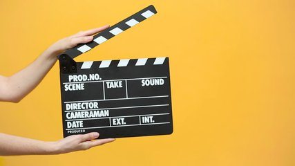 Close up female hold in hand classic director clear empty black film making clapperboard isolated on yellow orange background studio. Cinematography production concept. Copy space advertising mock up.