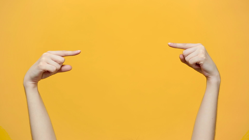 Woman hands pointing on copyspace isolated over yellow orange background in studio. Copy space for advertisement. With place for text or image promotional content. Advertising area, workspace mock up. | Shutterstock HD Video #1030421891