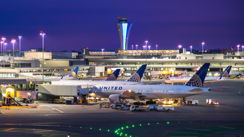 SAN FRANCISCO, CA - 2019: SFO International Airport Terminal Exterior Night Timelapse with United Airlines Commercial Jet Airplanes Parked and Moving from Gates and ATC Tower in the Background