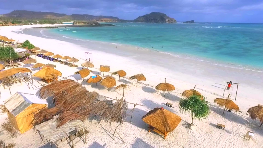 Flying over Kuta Beach Lombok. View of nice empty sandy beach with umbrella and beach chair, turquoise water Royalty-Free Stock Footage #1030423655
