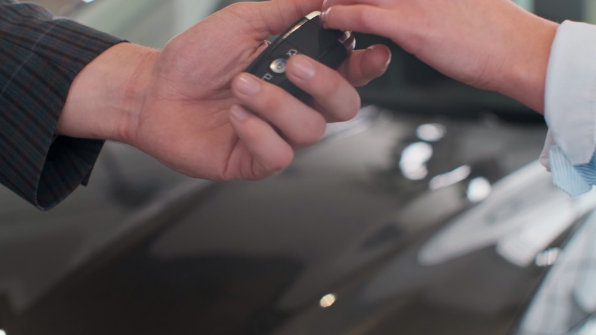 Famale hand gives a car keys to male hand in the car dealership close up. Unrecognized auto seller and a woman who bought a vehicle shake hands.