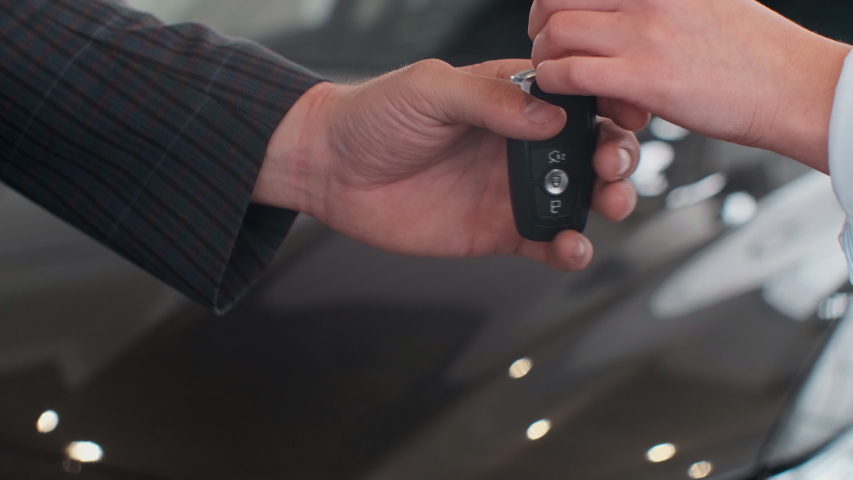 Famale hand gives a car keys to male hand in the car dealership close up. Unrecognized auto seller and a woman who bought a vehicle shake hands. Royalty-Free Stock Footage #1030426955