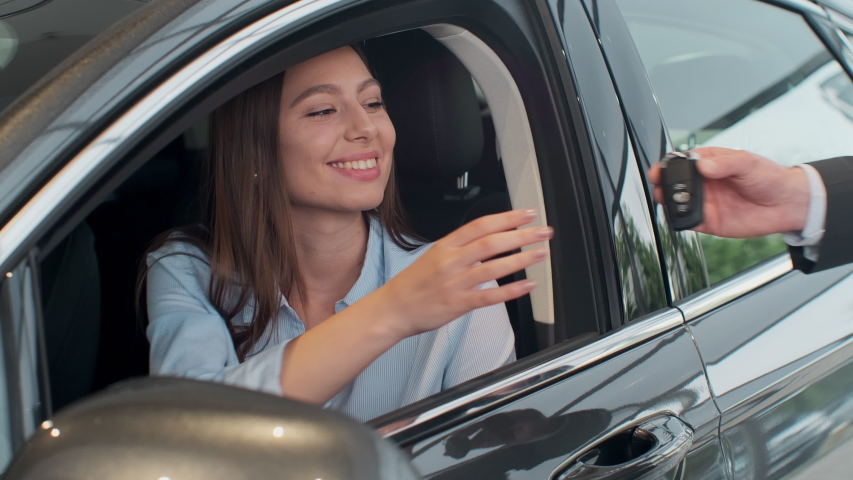 Sales manager handing over the keys to girl that sitting in the car.