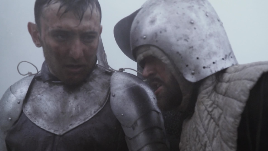Two medieval soldiers in armor, tired in the rain after the battle