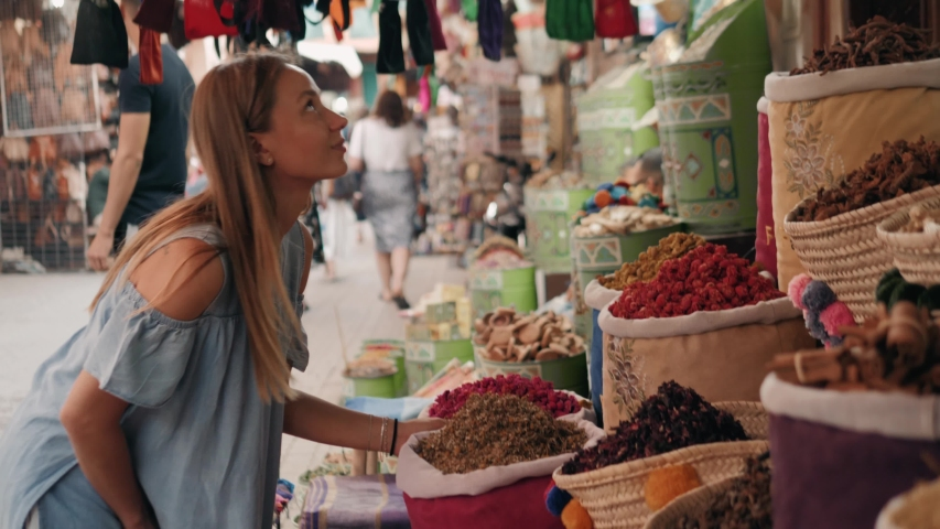 Woman walking on MAROCCAN MARRAKECH spices market. Woman walking on beautiful african arabian spices market and choose spices, travel tourist