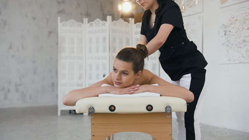 Professional female masseur making relaxing massage to young handsome woman lying on the massage table in modern spa salon. Dolly shot. #1030476596