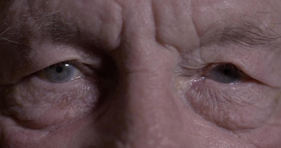 Seniors eyes close up, contemplative old caucasian man staring at camera. Macro