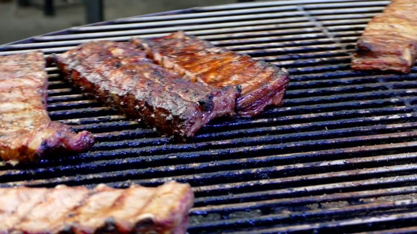 Meat ribs are roasted on a twisting grill. Picnic food. Barbecue on the nature. | Shutterstock HD Video #1030478255